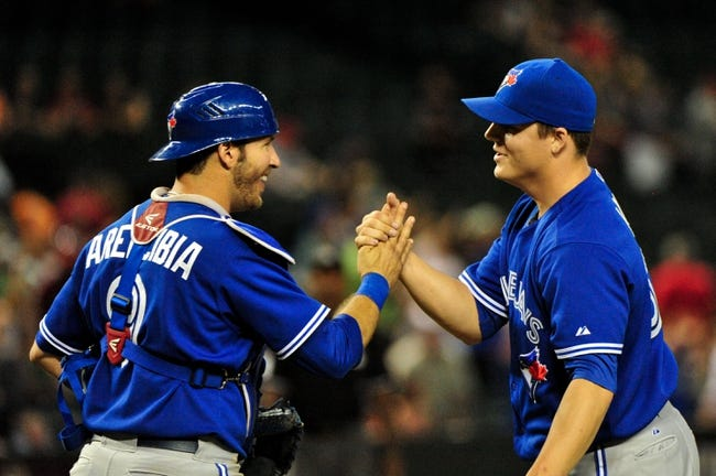 Sept 3, 2013; Phoenix, AZ, USA; Toronto Blue Jays relief pitcher Aaron Loup (62) celebrates with catcher J.P. Arencibia (9) after beating the Arizona Diamondbacks 10-4 at Chase Field. Mandatory Credit: Matt Kartozian-USA TODAY Sports
