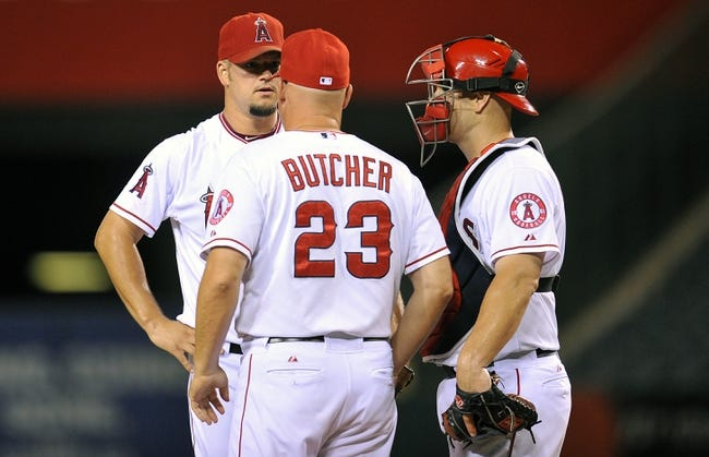 September 3, 2013; Anaheim, CA, USA; Los Angeles Angels pitching coach Mike Butcher (23) meets with starting pitcher Joe Blanton (55) and catcher Chris Iannetta (17) during a stoppage in play in the eighth inning at Angel Stadium of Anaheim. Mandatory Credit: Gary A. Vasquez-USA TODAY Sports