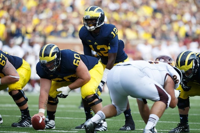 Aug 31, 2013; Ann Arbor, MI, USA; Michigan Wolverines quarterback Devin Gardner (12) gets set to run a play behind offensive linesman Jack Miller (60) against the Central Michigan Chippewas at Michigan Stadium. Mandatory Credit: Rick Osentoski-USA TODAY Sports