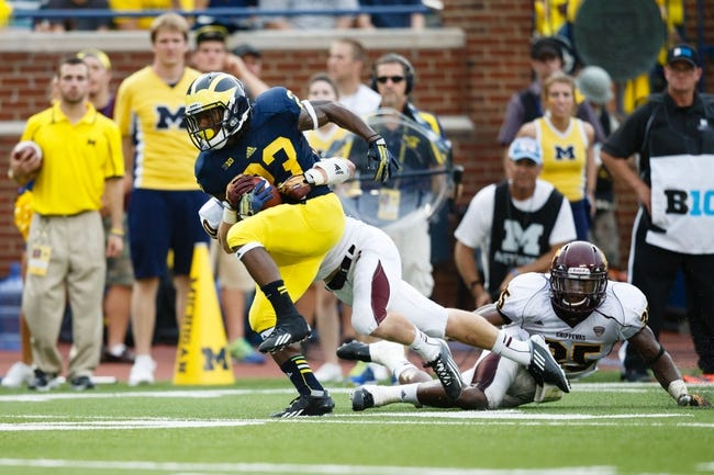 Aug 31, 2013; Ann Arbor, MI, USA; Michigan Wolverines wide receiver Dennis Norfleet (23) is tackled by Central Michigan Chippewas defensive back Kevin King (10) at Michigan Stadium. Mandatory Credit: Rick Osentoski-USA TODAY Sports