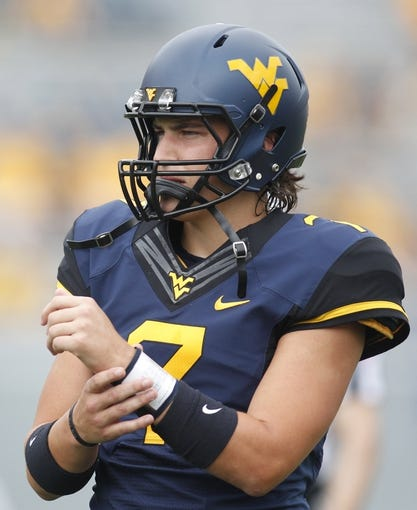 Aug 31, 2013; Morgantown, WV, USA; West Virginia Mountaineers quarterback Ford Childress (7) on the field before playing the William & Mary Tribe at Milan Puskar Stadium. The West Virginia Mountaineers won 24-17.  Mandatory Credit: Charles LeClaire-USA TODAY Sports