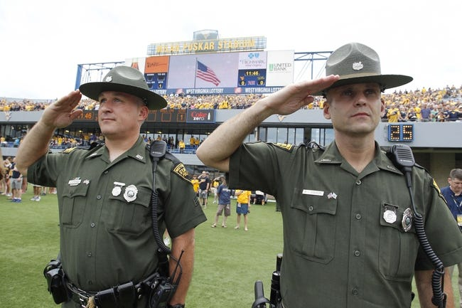 Aug 31, 2013; Morgantown, WV, USA; West Virginia state police officers G.S. Petsko (left) and M.L. Dickerson (right) stand at attention during the national anthem before the Mountaineers host the William & Mary Tribe at Milan Puskar Stadium. The West Virginia Mountaineers won 24-17. Mandatory Credit: Charles LeClaire-USA TODAY Sports