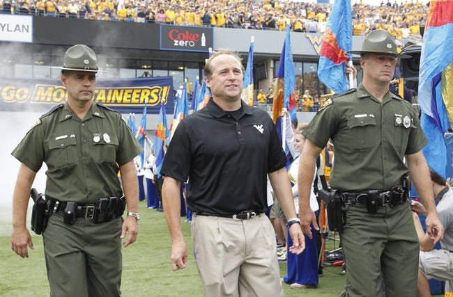 Aug 31, 2013; Morgantown, WV, USA; West Virginia Mountaineers head coach Dana Holgorsen (center) takes the field during the first quarter to play the William & Mary Tribe at Milan Puskar Stadium. The West Virginia Mountaineers won 24-17.  Mandatory Credit: Charles LeClaire-USA TODAY Sports