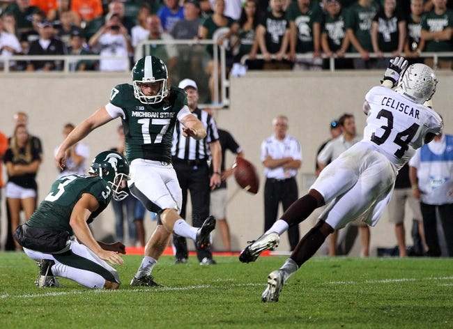 Aug 30, 2013; East Lansing, MI, USA; Michigan State Spartans kicker Kevin Muma (17) attempts to kick a field goal out of the hold by punter Mike Sadler (3) during 1st half of a game at Spartan Stadium.   Mandatory Credit: Mike Carter-USA TODAY Sports