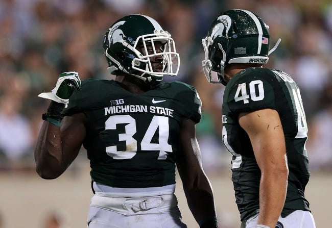 Aug 30, 2013; East Lansing, MI, USA; Michigan State Spartans linebacker Taiwan Jones (34) and linebacker Max Bullough (40) talk during 2nd  half of a game at Spartan Stadium. MSU won 26-13.   Mandatory Credit: Mike Carter-USA TODAY Sports