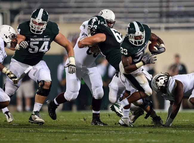 Aug 30, 2013; East Lansing, MI, USA; Michigan State Spartans running back Jeremy Langford (33) runs the ball against the Western Michigan Broncos during 1st half of a game at Spartan Stadium.   Mandatory Credit: Mike Carter-USA TODAY Sports