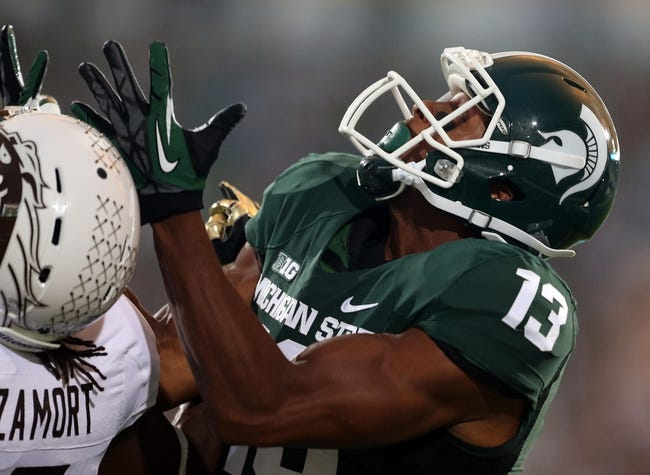 Aug 30, 2013; East Lansing, MI, USA; Michigan State Spartans wide receiver Bennie Fowler (13) attempts to catch a ball against Western Michigan Broncos cornerback Ronald Zamort (7) during 1st quarter of a game at Spartan Stadium.   Mandatory Credit: Mike Carter-USA TODAY Sports