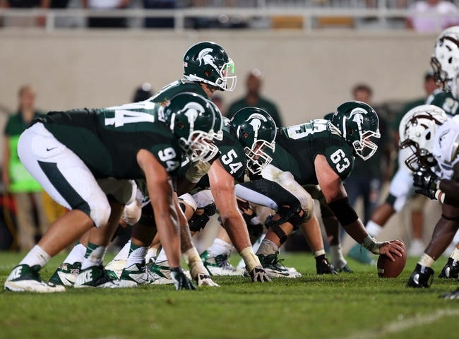 Aug 30, 2013; East Lansing, MI, USA; Michigan State Spartans center Travis Jackson (63) prepares to snap the ball to quarterback Andrew Maxwell (10) during 2nd  half of a game at Spartan Stadium. MSU won 26-13.   Mandatory Credit: Mike Carter-USA TODAY Sports