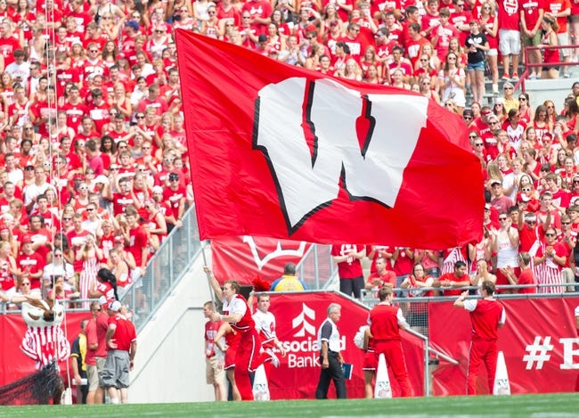 Aug 31, 2013; Madison, WI, USA; A Wisconsin Badgers cheerleaders waves a Wisconsin flag during the game against the Massachusetts Minutemen at Camp Randall Stadium.  Wisconsin won 45-0.  Mandatory Credit: Jeff Hanisch-USA TODAY Sports