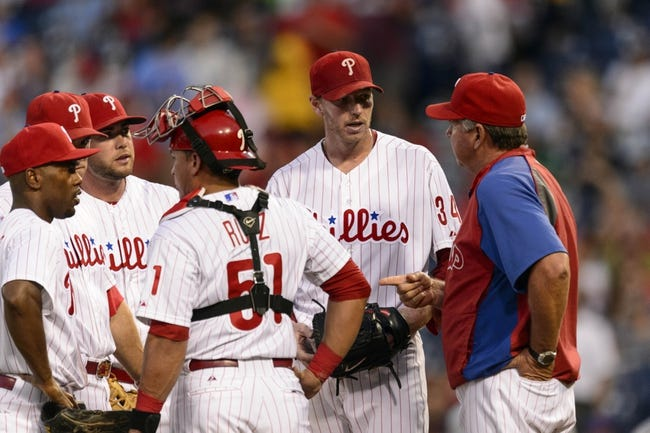 Sep 4, 2013; Philadelphia, PA, USA; Philadelphia Phillies pitching coach Rich Dubee (30) talks with pitcher Roy Halladay (34) during the first inning against the Washington Nationals at Citizens Bank Park. Mandatory Credit: Howard Smith-USA TODAY Sports