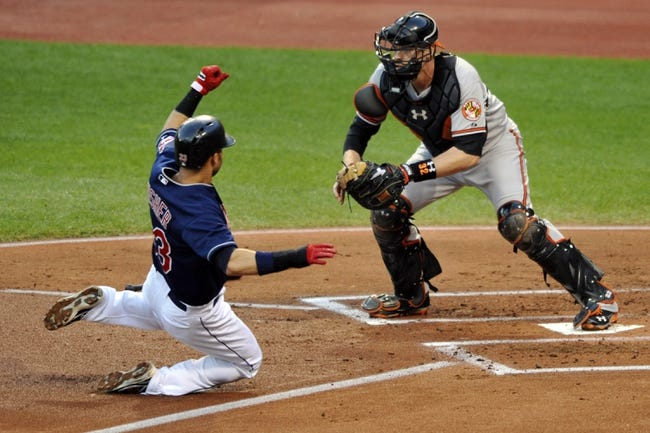 Sep 4, 2013; Cleveland, OH, USA; Baltimore Orioles catcher Matt Wieters (32) forces out Cleveland Indians first baseman Nick Swisher (33) at home plate in the first inning at Progressive Field. Mandatory Credit: David Richard-USA TODAY Sports