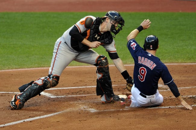 Sep 4, 2013; Cleveland, OH, USA; Baltimore Orioles catcher Matt Wieters (32) tags out Cleveland Indians left fielder Ryan Raburn (9) in the first inning at Progressive Field. Mandatory Credit: David Richard-USA TODAY Sports