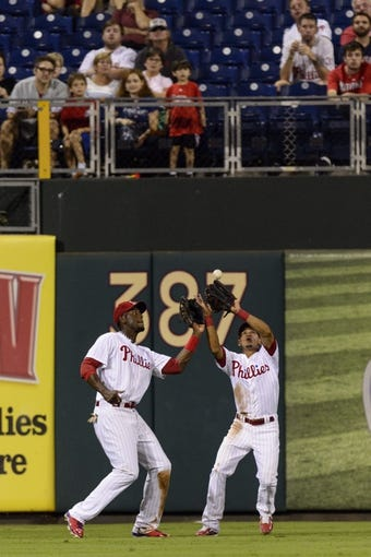 Sep 4, 2013; Philadelphia, PA, USA; Philadelphia Phillies center fielder Cesar Hernandez (16) makes the catch in front of left fielder fielder John Mayberry (15) during the third inning against the Washington Nationals at Citizens Bank Park. Mandatory Credit: Howard Smith-USA TODAY Sports