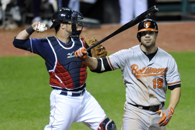 Sep 4, 2013; Cleveland, OH, USA; Cleveland Indians catcher Yan Gomes (10) throws to third base as Baltimore Orioles first baseman Chris Davis (19) reacts after striking out in the eighth inning at Progressive Field. Mandatory Credit: David Richard-USA TODAY Sports