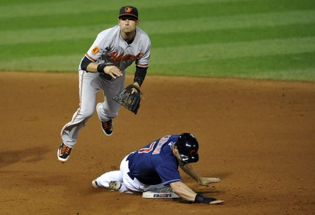 Sep 4, 2013; Cleveland, OH, USA; Cleveland Indians left fielder Matt Carson (7) slides into second base as Baltimore Orioles shortstop J.J. Hardy (2) completes a double play in the eighth inning at Progressive Field. Mandatory Credit: David Richard-USA TODAY Sports