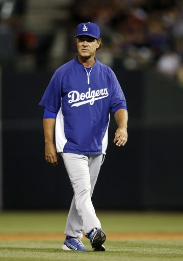 Sep 4, 2013; Denver, CO, USA; Los Angeles Dodgers manager Don Mattingly walks back to the dugout after arguing a call on the field during the third inning against the Colorado Rockies at Coors Field. Mandatory Credit: Chris Humphreys-USA TODAY Sports