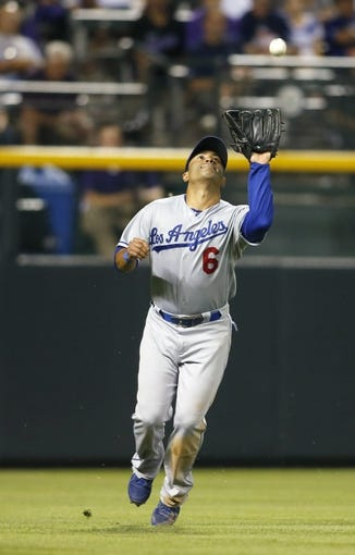 Sep 4, 2013; Denver, CO, USA; Los Angeles Dodgers left fielder Jerry Hairston (6) catches a fly ball during the fourth inning against the Colorado Rockies at Coors Field. Mandatory Credit: Chris Humphreys-USA TODAY Sports