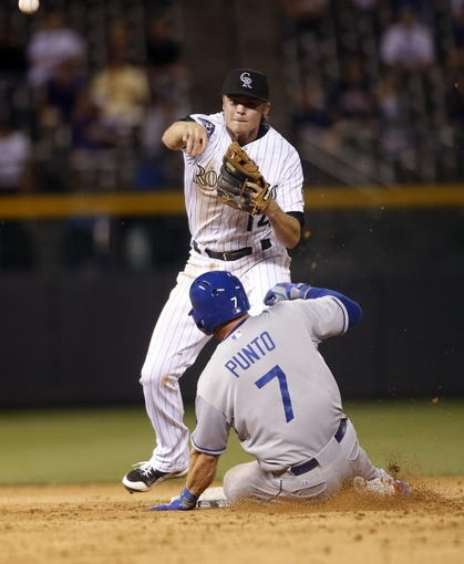 Sep 4, 2013; Denver, CO, USA; Colorado Rockies second baseman Josh Rutledge (14) turns the double play at second base to end the game against the Los Angeles Dodgers at Coors Field. The Rockies won 7-5.  Mandatory Credit: Chris Humphreys-USA TODAY Sports