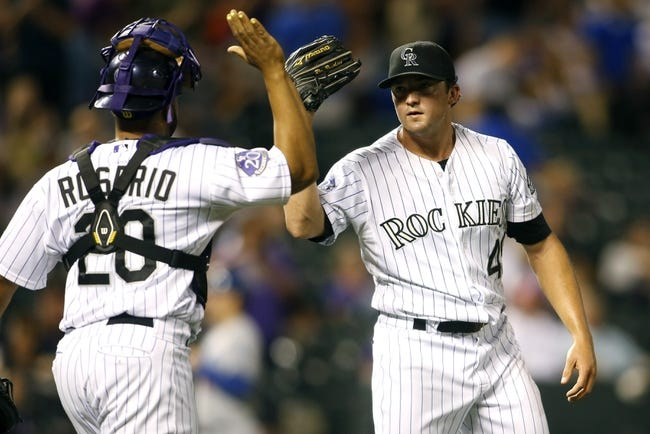 Sep 4, 2013; Denver, CO, USA; Colorado Rockies pitcher Rex Brothers (49) and catcher Wilin Rosario (20) celebrate after the game against the Los Angeles Dodgers at Coors Field. The Rockies won 7-5.  Mandatory Credit: Chris Humphreys-USA TODAY Sports