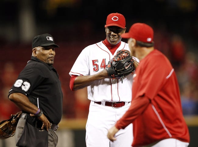Sep 5, 2013; Cincinnati, OH, USA; Cincinnati Reds relief pitcher Aroldis Chapman (54) is checked out by Cincinnati Reds pitching coach Bryan Price (38) and umpire Laz Diaz (63) after catching a hit up the middle during the ninth inning against the St. Louis Cardinals at Great American Ball Park. The Reds defeated the Cardinals 6-2. Mandatory Credit: Frank Victores-USA TODAY Sports