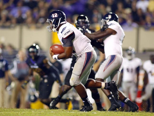 September 5, 2013; Greenville, NC, USA;  Florida Atlantic quarterback Jacquez Johnson (12) runs with the ball against East Carolina at Dowdy-Ficklen Stadium. East Carolina Pirates defeated the Florida Atlantic Owls 31-13. Mandatory Credit: James Guillory-USA TODAY Sports