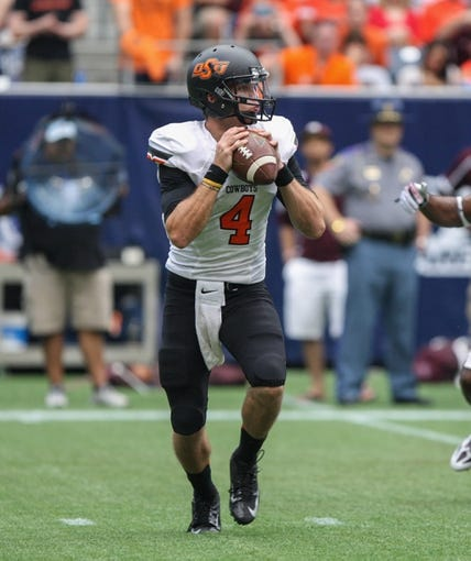 Aug 31, 2013; Houston, TX, USA; Oklahoma State Cowboys quarterback J.W. Walsh (4) looks for an open receiver during the second quarter against the Mississippi State Bulldogs at Reliant Stadium. Mandatory Credit: Troy Taormina-USA TODAY Sports