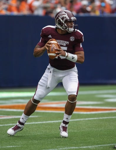 Aug 31, 2013; Houston, TX, USA; Mississippi State Bulldogs quarterback Dak Prescott (15) looks for an open receiver during the fourth quarter against the Oklahoma State Cowboys at Reliant Stadium. Mandatory Credit: Troy Taormina-USA TODAY Sports