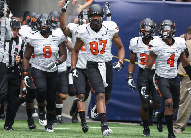 Aug 31, 2013; Houston, TX, USA; Oklahoma State Cowboys wide receiver Tracy Moore (87) leads his team onto the field before a game against the Mississippi State Bulldogs at Reliant Stadium. Mandatory Credit: Troy Taormina-USA TODAY Sports
