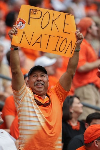 Aug 31, 2013; Houston, TX, USA; Oklahoma State Cowboys fan Mike Cortinaz holds a sign during a game Mississippi State Bulldogs at Reliant Stadium. Mandatory Credit: Troy Taormina-USA TODAY Sports