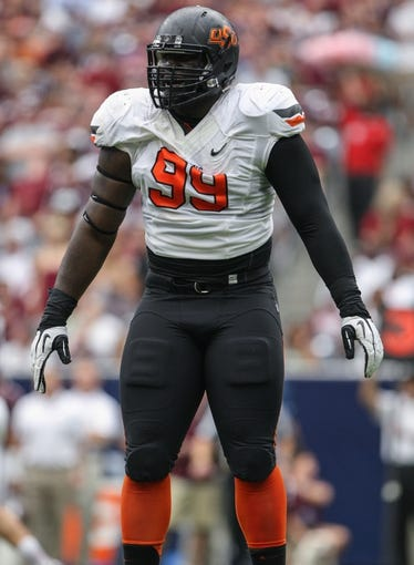 Aug 31, 2013; Houston, TX, USA; Oklahoma State Cowboys defensive tackle Calvin Barnett (99) reacts after a play during the second quarter against the Oklahoma State Cowboys at Reliant Stadium. Mandatory Credit: Troy Taormina-USA TODAY Sports