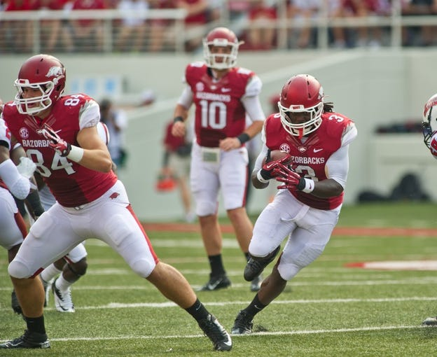 Aug 31, 2013; Fayetteville, AR, USA; Arkansas Razorback running back Alex Collins (3) carries the ball as tight end Henry Hunter (84) blocks and quarterback Brandon Allen (10) looks on during a game against the Louisiana Ragin' Cajuns at Donald W. Reynolds Razorback Stadium. Arkansas defeated Louisiana 34-14. Mandatory Credit: Beth Hall-USA TODAY Sports