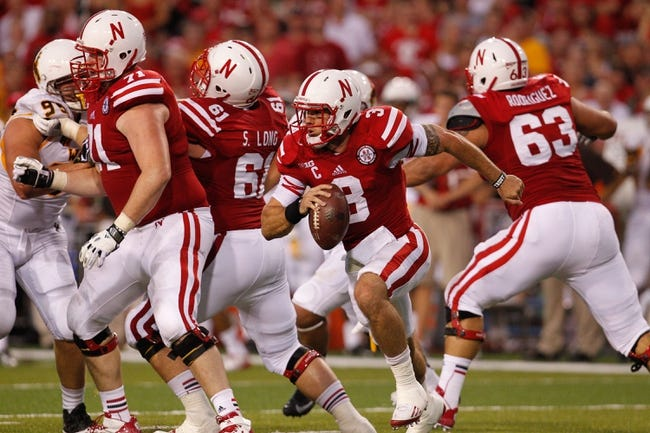 Aug 31, 2013; Lincoln, NE, USA; Nebraska Cornhuskers quarterback Taylor Martinez (3) runs behind his linemen Jeremiah Sirles (71), Spencer Long (61) and Andrew Rodriguez (63) against the Wyoming Cowboys at Memorial Stadium. Nebraska won 37-34. Mandatory Credit: Bruce Thorson-USA TODAY Sports