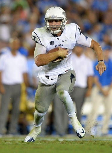 Aug 31, 2013; Pasadena, CA, USA; Nevada Wolf Pack quarterback Cody Fajardo (17) scores on a 19-yard touchdown run against the UCLA Bruins at the Rose Bowl. UCLA defeated Nevada 58-20. Mandatory Credit: Kirby Lee-USA TODAY Sports