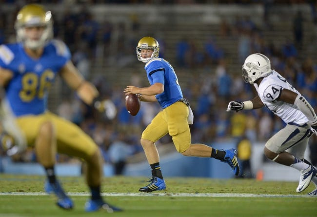 Aug 31, 2013; Pasadena, CA, USA; UCLA Bruins quarterback Jerry Neuheisel (11) is pressured by Nevada Wolf Pack defensive end Lenny Jones (94) at the Rose Bowl. UCLA defeated Nevada 58-20. Mandatory Credit: Kirby Lee-USA TODAY Sports