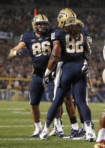 Sep 2, 2013; Pittsburgh, PA, USA; Pittsburgh Panthers tight end Manasseh Garner (82) reacts with tight end J.P. Holtz (86) after Garner scored a four yard touchdown against the Florida State Seminoles during the first quarter at Heinz Field. The Florida State Seminoles won 41-13. Mandatory Credit: Charles LeClaire-USA TODAY Sports