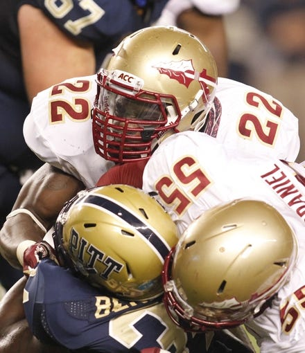 Sep 2, 2013; Pittsburgh, PA, USA; Florida State Seminoles linebacker Telvin Smith (22) and defensive tackle Jacobbi McDaniel (55) tackle Pittsburgh Panthers running back Isaac Bennett (bottom) during the second quarter at Heinz Field. The Florida State Seminoles won 41-13. Mandatory Credit: Charles LeClaire-USA TODAY Sports
