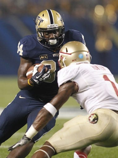Sep 2, 2013; Pittsburgh, PA, USA; Pittsburgh Panthers running back Isaac Bennett (34) carries the ball against Florida State Seminoles defensive back Tyler Hunter (1) during the first quarter against at Heinz Field. The Florida State Seminoles won 41-13. Mandatory Credit: Charles LeClaire-USA TODAY Sports