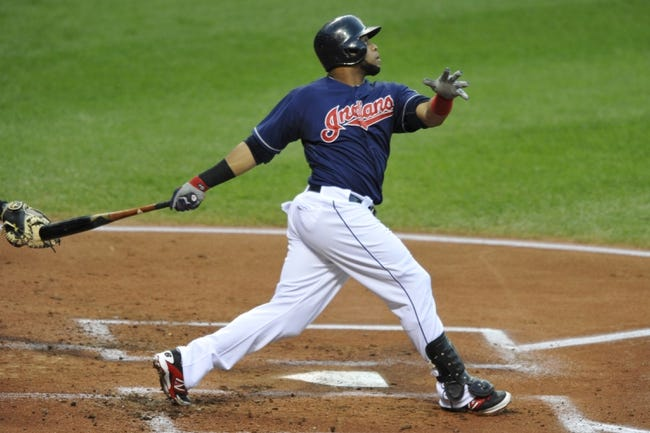 Sep 6, 2013; Cleveland, OH, USA; Cleveland Indians catcher Carlos Santana (41) hits an RBI sacrifice fly ball in the first inning against the New York Mets at Progressive Field. Mandatory Credit: David Richard-USA TODAY Sports