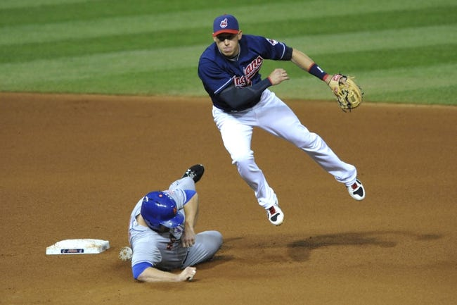 Sep 6, 2013; Cleveland, OH, USA; Cleveland Indians shortstop Asdrubal Cabrera (13) turns a double play over New York Mets first baseman Lucas Duda (21) in the fourth inning at Progressive Field. Mandatory Credit: David Richard-USA TODAY Sports