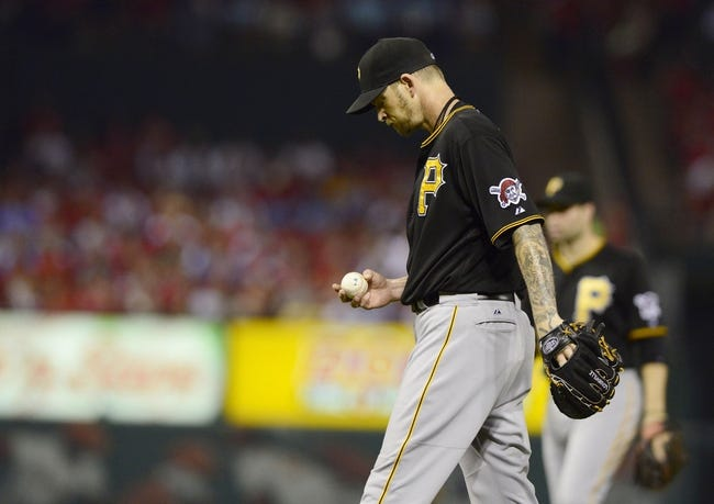 Sep 6, 2013; St. Louis, MO, USA; Pittsburgh Pirates starting pitcher A.J. Burnett (34) looks at the baseball after giving up a one run double to St. Louis Cardinals right fielder Carlos Beltran (not pictured) during the third inning at Busch Stadium. Mandatory Credit: Jeff Curry-USA TODAY Sports