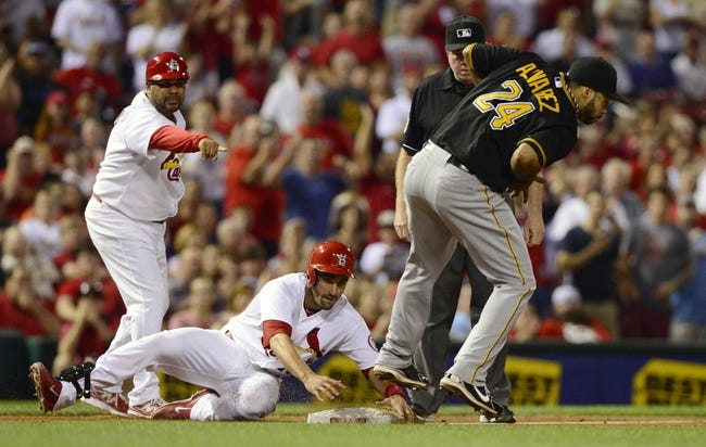 Sep 6, 2013; St. Louis, MO, USA; St. Louis Cardinals second baseman Matt Carpenter (13) slides safely into third for a triple as Pittsburgh Pirates third baseman Pedro Alvarez (24) fields the throw during the third inning at Busch Stadium. Mandatory Credit: Jeff Curry-USA TODAY Sports