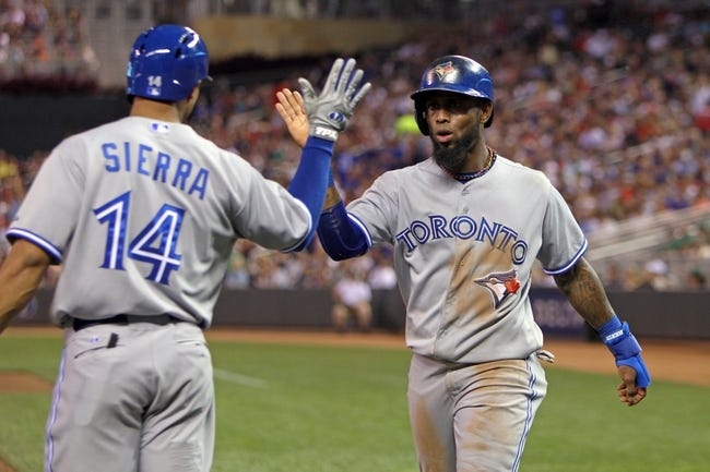 Sep 6, 2013; Minneapolis, MN, USA; Toronto Blue Jays shortstop Jose Reyes (7) is congratulated by outfielder Moises Sierra (14) after scoring a run during the third inning against the Minnesota Twins at Target Field. Mandatory Credit: Brace Hemmelgarn-USA TODAY Sports