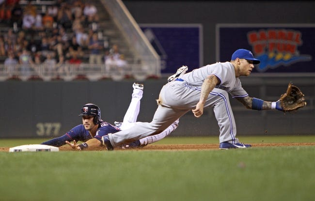 Sep 6, 2013; Minneapolis, MN, USA; Minnesota Twins third baseman Trevor Plouffe (24) slides safely into third base past Toronto Blue Jays third baseman Brett Lawrie (13) during the eighth inning at Target Field. The Blue Jays defeated the Twins 6-5. Mandatory Credit: Brace Hemmelgarn-USA TODAY Sports