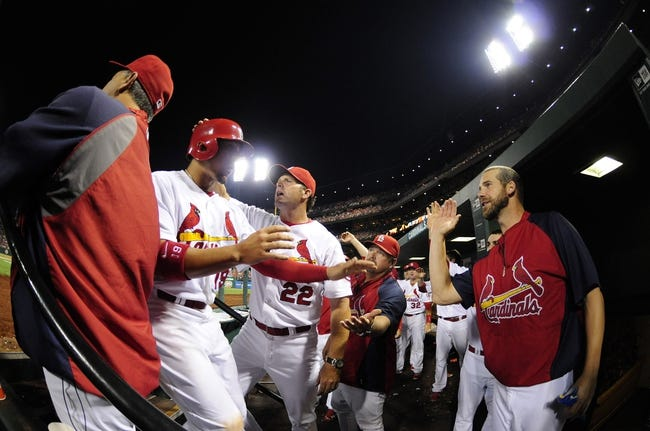 Sep 6, 2013; St. Louis, MO, USA; St. Louis Cardinals center fielder Jon Jay (left) is congratulated by manager Mike Matheny (22) and Chris Carpenter (right) after scoring on a double by left fielder Matt Holliday (not pictured) during the third inning against the Pittsburgh Pirates at Busch Stadium. Mandatory Credit: Jeff Curry-USA TODAY Sports