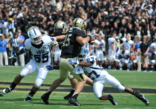 Sep 7, 2013; West Lafayette, IN, USA; Purdue Boilermakers quarterback Rob Henry (15) is sacked by Indiana State Sycamores defensive back Lonnell Brown Jr. (27) and defensive lineman Connor Underwood (55) in the first half at Ross Ade Stadium. Mandatory Credit: Sandra Dukes-USA TODAY Sports