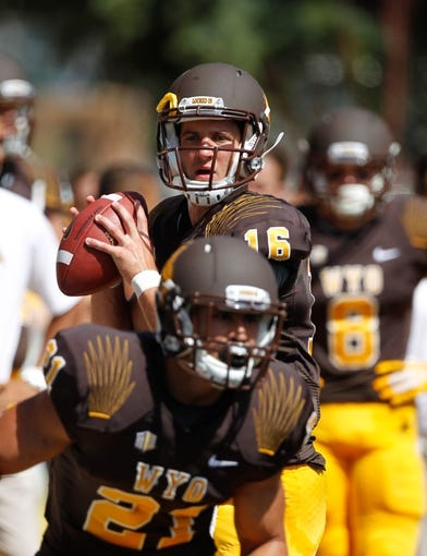 Sep 7, 2013; Laramie, WY, USA; Wyoming Cowboys quarterback Brett Smith (16) warms up before the game between the Wyoming Cowboys and the Idaho Vandals at War Memorial Stadium. Mandatory Credit: Troy Babbitt-USA TODAY Sports
