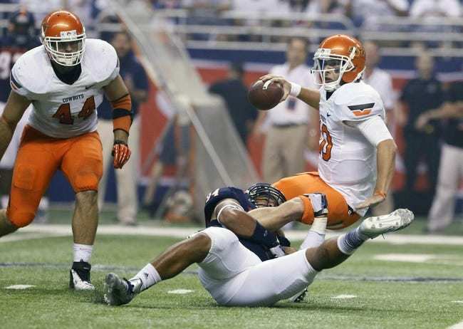 Sep 7, 2013; San Antonio, TX, USA; Texas-San Antonio Roadrunners defensive end Brooks, Codie (bottom) sacks Oklahoma State Cowboys quarterback Chelf, Clint (10) during the second half  at Alamodome. Oklahoma State Cowboys beat Texas-San Antonio Roadrunners 56-35. Mandatory Credit: Soobum Im-USA TODAY Sports
