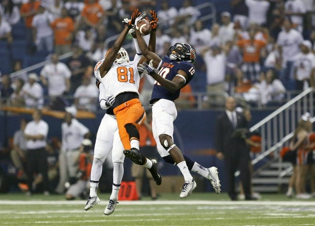 Sep 7, 2013; San Antonio, TX, USA; Oklahoma State Cowboys wide receiver Seales, Jhajuan (81) catches the ball as Texas-San Antonio Roadrunners safety King, Brian (right) and corner back Starling, Darrien (left) defend during the second half  at Alamodome. Oklahoma State Cowboys beat Texas-San Antonio Roadrunners 56-35. Mandatory Credit: Soobum Im-USA TODAY Sports