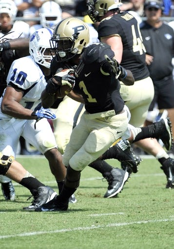 Sep 7, 2013; West Lafayette, IN, USA;  Purdue Boilermakers running back Akeem Hunt (1) looks for room to run past Indiana State Sycamores linebacker Kendall Walker (10)  in the 2nd half at Ross Ade Stadium. Mandatory Credit: Sandra Dukes-USA TODAY Sports