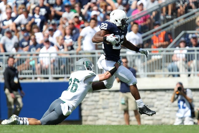 Sep 7, 2013; University Park, PA, USA; Penn State Nittany Lions running back Akeel Lynch (22) leaps over Eastern Michigan Eagles defensive back Mycal Swaim (26) during the fourth quarter at Beaver Stadium. Penn State defeated Eastern Michigan 45-7. Mandatory Credit: Matthew O'Haren-USA TODAY Sports